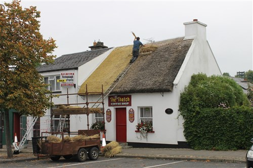 A thatcher replaces the roof on The Thatch Coffee Shop, Belleek, County Fermanagh