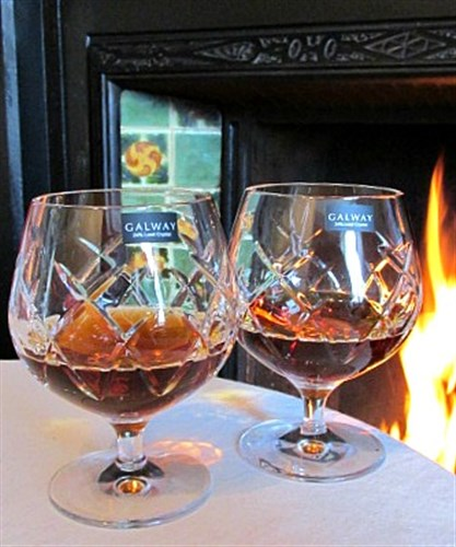 Galway Crystal Brandy Glassed filled with cognac in front of open fire
