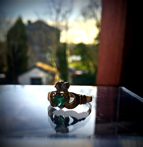 emeral Gold Claddagh ring photographed in window overlooking Belleek Pottery and River Erne