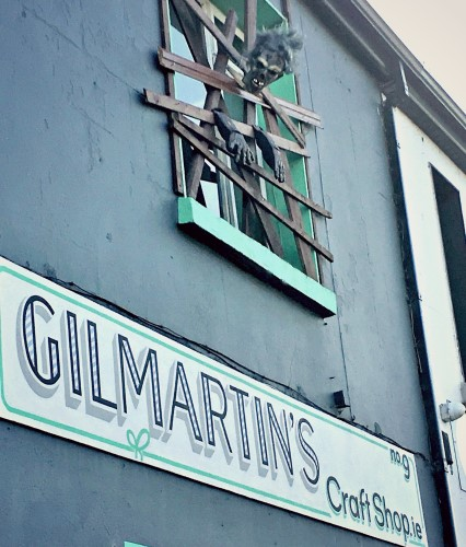 Photo of Phil The Zombie breaking out through a boarded up window at Gilmartin's Craft Shop, Belleek