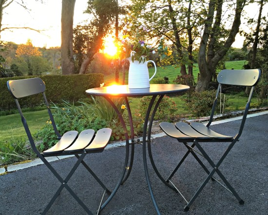 garden at sunset. Table for two set with a vase of wildflowers.